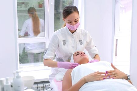 Cosmetologist in gloves washes cleans clients woman face wiping with napkins. Beautician making massaging beauty facial skincare procedure to patient in clinic. Beauty industry concept.