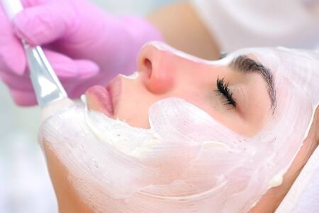 Cosmetologist is applying white mask on woman client face in beauty clinic. Portrait of woman, side view. Beautician making beauty facial skincare procedure to patient. Beauty industry concept. Stok Fotoğraf