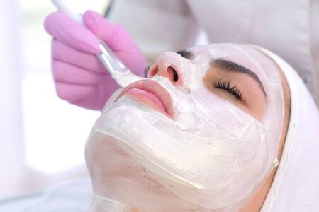 Cosmetologist is applying white mask on woman client face in beauty clinic. Portrait of woman, closeup view. Beautician making beauty facial skincare procedure to patient. Beauty industry concept.