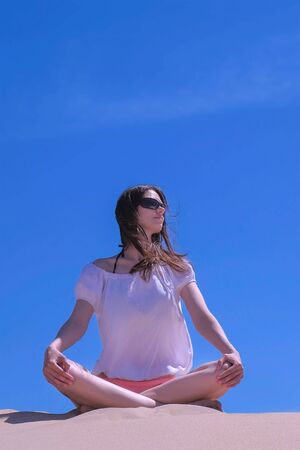 Woman in sunglasses is meditating on vacation. Travel tourist sitting at seashore. Girl meditate looks around sits sandy beach on blue sky background yoga pose. Summer wind blow. Vertical