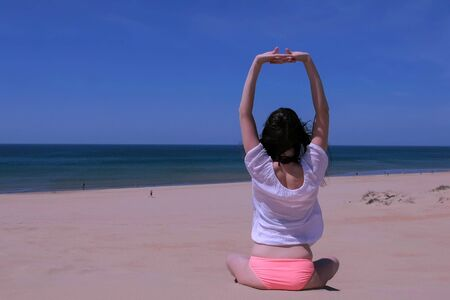 Woman practices yoga sits in lotus pose on sea sandy beach windy day, back view. She stretches hands up wearing in swimsuit, sunglasses and blouse. Travel tourism on vacation. Sport outdoor comcept. Stok Fotoğraf