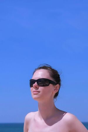 Portrait young woman sunbathing stand on beach on sea and blue sky background. Brunette girl is in sunglasses and bikini, front view. Turist travel summer vacation. Vertical