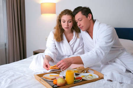 Young family couple having vacations together. Man and woman are eating breakfast from wooden tray together sitting in bed in hotel room. They are making sandwiches. Luxury resting concept.