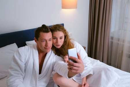 Young family couple man and woman in bathrobes making selfie photos on smartphone eating breakfast in hotel room. Luxury resting concept. They are eating sandwiches and talking in bed. Stok Fotoğraf