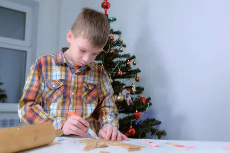 Boy is making gingerbread cookies cutting dough on Christmas tree background. Boy is using knife to cut cookies. Cooking baking cookies in New Year time. Sweet homemade bakery.