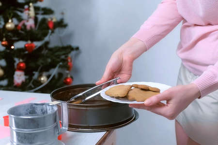 Woman is putting gingerbread cookies from tray to plate using tongs, hands closeup. Cooking baking cookies in New Year time on Christmas tree background. Sweet homemade bakery.