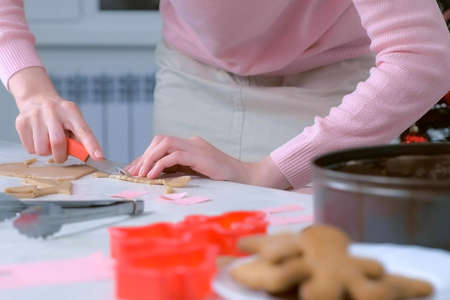 Woman is cutting parts for gingerbread house from dough and putting it in baking tray, hands closeup. Cooking baking cookies in New Year time. Sweet homemade bakery.