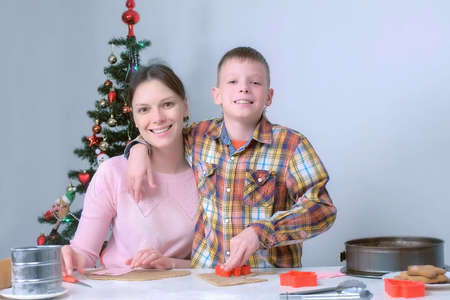 Mom and son are making gingerbread cookies lookind at camera and smiling, front view. Family Christmas traditions. Cooking baking cookies in New Year time. Sweet homemade bakery. Stok Fotoğraf