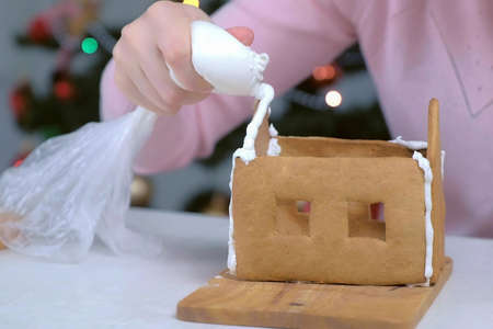 Woman making gingerbread house glues details with sugar sweet icing, hands closeup. Cooking homemade gingerbread house for Christmas holidays. New Year family traditions.