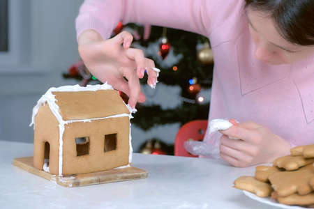 Portrait of woman making gingerbread house glues details with sugar sweet icing. Cooking homemade gingerbread house for Christmas holidays. New Year family traditions. Doing roof and walls. Stok Fotoğraf