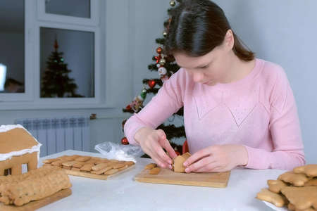 Portrait of woman making gingerbread house glues parts with sugar sweet icing. Cooking and decorating homemade gingerbread house for Christmas holidays. New Year family traditions. Cookies on plate.