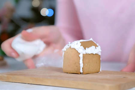 Woman is making gingerbread house glues parts with sugar sweet icing, hands closeup. Cooking and decorating homemade gingerbread house for Christmas holidays. New Year family traditions.