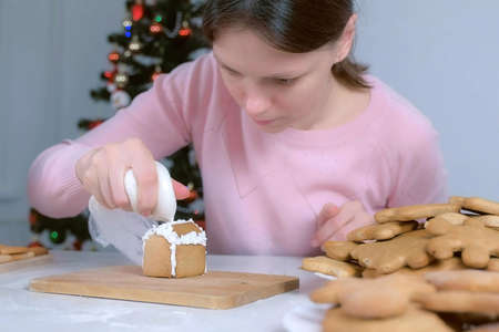 Woman making gingerbread house glues parts with sugar sweet icing. Cooking and decorating homemade gingerbread house for Christmas holidays. New Year family traditions. Cookies on plate. Stok Fotoğraf