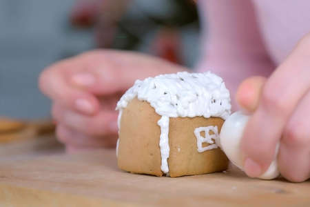 Woman is decorating gingerbread house with sugar sweet icing, hands closeup. Cooking, baking homemade gingerbread house for Christmas holidays. Painting window. New Year family traditions. Stok Fotoğraf