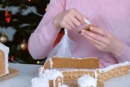 Woman is decorating christmas gingerbread man cookie with sugar sweet icing, hands closeup. Homemade gingerbread cookies for Christmas holidays. New Year family traditions. Stok Fotoğraf