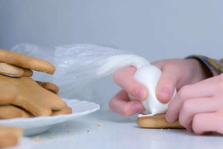 Child boy is decorating christmas cookie of tree shape with sugar sweet icing, hands closeup. Cooking, baking homemade gingerbread cookies for Christmas holidays. New Year family traditions.