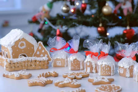 Gingerbread houses and cookies in package for Christmas on table on Christmas tree background with blinking garlands. Preparing presents, gifts, New Year festive atmosphere.