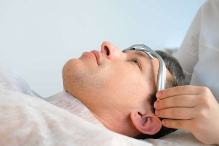 Chiropractor doctor is putting on electronic headband from migraine on mans forehead. Treatment of headaches with electric current in clinic on procedure with manual physiotherapist.