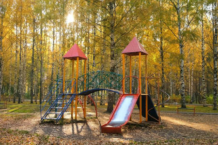 Publics playground for children with slide in autumn city park. Yellow foliage covering the ground, beautiful trees around the playground. 免版税图像