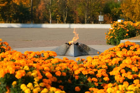 Monument of eternal fire in honor of victory day in world war on square in autumn park among orange marigold beautiful flowers, closeup view. 免版税图像