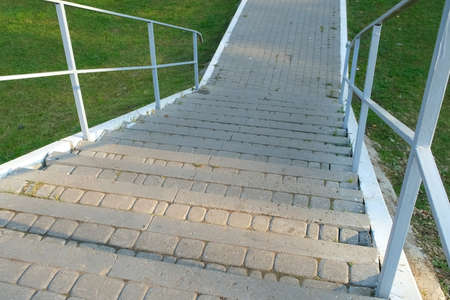 Gentrified territory. Stairs in the Park among the green lawn grass, infrastructure in the city, closeup view. 免版税图像