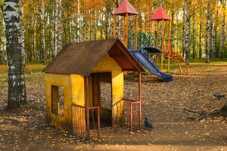 Public playground for children in autumn city park with beautiful yellow trees. Yellow foliage covering the ground, beautiful trees around the playground.