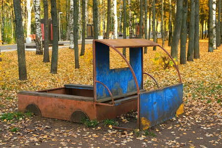 Publics playground for children with wooden lorry in autumn city park with beautiful yellow trees. Yellow foliage covering the ground, beautiful trees around the playground. 免版税图像
