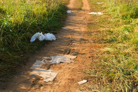 Garbage cartons and packages on a rural ground road among grass, closeup view. The concept of environmental pollution by food packaging and garbage.