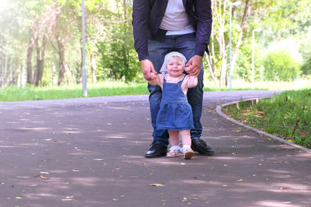 Father learning his daugter to walk outdoors. Baby girl is trying to go making first steps holding dads hands in city park. Happy girl of one year old. Fatherhood and babycare concept.