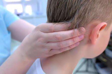 Doctor professional masseur making therapy head massage to teen boy in clinic, closeup back view. Massagist massaging child boys head. Rehabilitation medicine treatment for children. Stock Photo