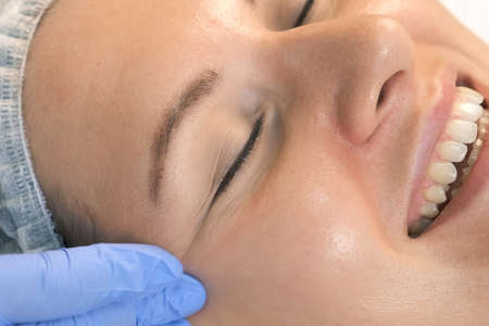 Beautician is making cure procedure on patients face. Cosmetologist is applying yellow peeling on womans face massaging movements in beauty clinic, chin closeup. Drops of medicine on womans chin.