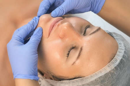 Beautician is doing cure procedures on client face in cosmetology clinic. Face of smiling woman closeup. Cosmetologist doctor is making myoplastic anti-aging facial massage to woman in beauty clinic.