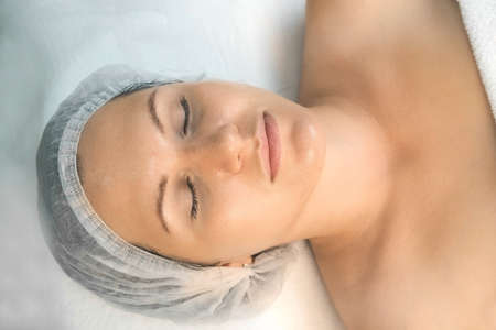 Woman on facial procedure in cosmetology clinic, closeup face, top view. She is lying on couch with closed eyes with yellow peeling on her face. Treatment, cure of face skin for young female. Imagens