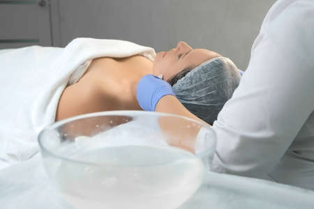 Cosmetologist doctor wiping womans face using antibacterial napkins after peeling, view from back. Doctor is making beauty procedure in cosmetology clinic. Care about patients face skin.