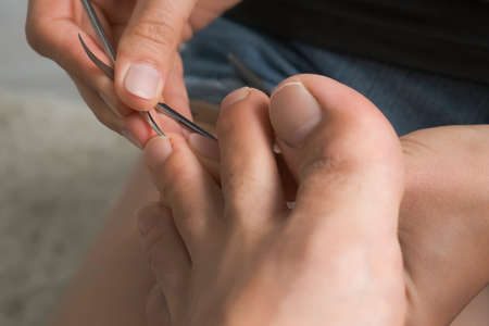 Woman is polishing man husbands nails on toes using file, closeup view. She sitting on floor at home and making pedicure. Hygiene and care for feet. She removes dirt from under the nails.