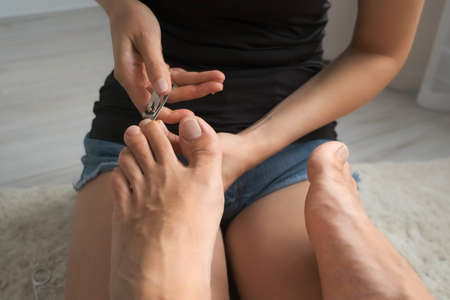 Woman is cutting nails nippers and polishing with file on husbands toes, closeup view. She is sitting on floor on carpet at home and making pedicure. Hygiene and care for feet. 스톡 콘텐츠