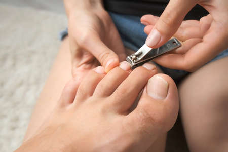 Woman is cutting mans nails on toes using nippers, closeup hands and feet view. She is sitting on floor on carpet at home and making pedicure. Hygiene and care for feet.