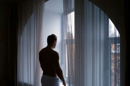 Silhouette of young man in white towel in hotel near window in morning in city, side view. Traveling, resting, tourism concept. The hotel is located a historic building.