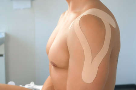 Kinesiology tapes on mans shoulder and hand for fixation of muscles, closeup. Using of tapes in medicine for fixation of muscles and joints. Recovery and rehabilitation after injury or sport.