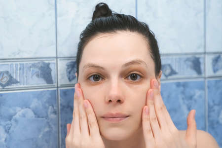 Portrait of young woman is applying hyaluronic acid on face skin taking a bath with foam. Rejuvenating and moisturizing, regenerating treatment at home. Wellness, body care and self love concept. Standard-Bild