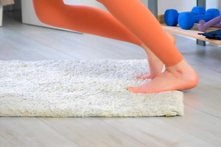 Woman in sportswear is warming her feet practicing youga doing exercises at home, closeup legs. Sport, fitness, training, stretching, workout, yoga and wellness concept.