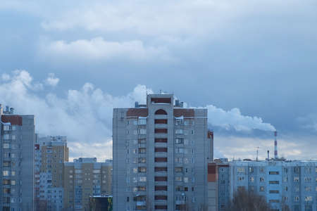 City landscape with houses and factory with a chimney and smoke in background. Winter evening in city. Production in a residential area, environmental and air pollution and danger to life and health.