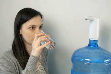 Woman is pouring water into glass from an automatic water cooler and drinking it. She is pouring fresh clear water from big blue gallon to glass. Clean drinking bottled water from the well.