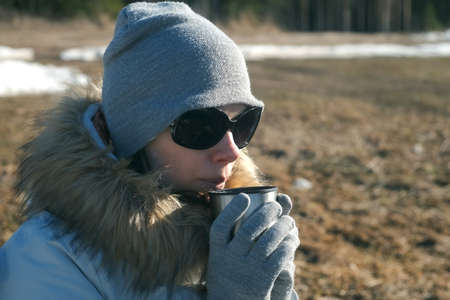 Portrait of young woman in hat, sun glasses and fur jacket is drinking tea on nature. Food and drink on nature in camping. Traveler enjoying hot tea from on hiking at cold weather.