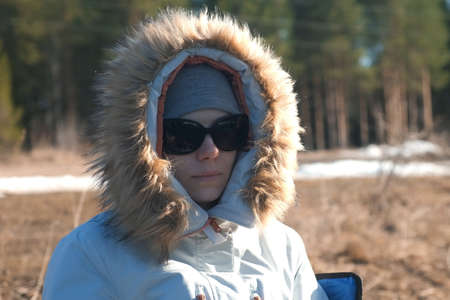 Portrait of young woman in hat, sun glasses and fur jacket on nature. She basks in the first rays of the spring sun. Resting and relaxing on wild nature. Melting snow covers last years grass. Standard-Bild