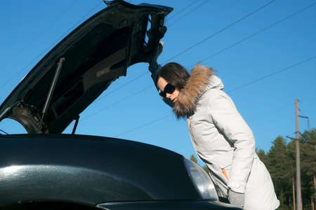 Young woman in a jacket opens the hood of her car from the front. Puzzled woman near broken car, looking at motor under open hood, breakdown car on forest road on blue sky background.