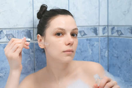 Young woman is applying hyaluronic acid on face skin taking a bath with foam. Rejuvenating and moisturizing, regenerating treatment at home. Wellness, body care and self love concept. Standard-Bild