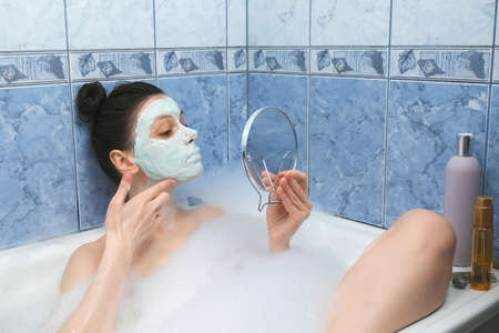 Portrait og young woman is applying alginate mask in bathr with foam looking at small mirror at home. Spa beauty treatment, anti-aging procedure face skin. Wellness, skincare and self love concept.