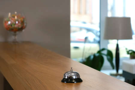 Reception at the hotel with a bell on a wooden table, closeup view. Place for reception and accommodation of guests in the hall of the hotel. Modern interrior.
