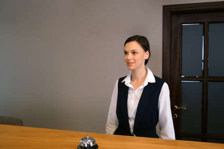 Smiling woman receptionist in uniform on reception at the hotel with a bell on a wooden table. Place for reception and accommodation of guests in the hall of the hotel. Modern interrior and service.